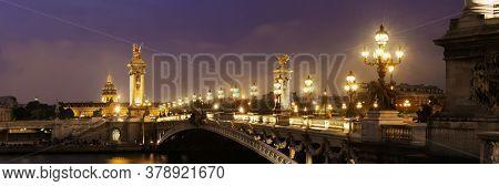 Alexandre III bridge night view panorama with Napoleon's tomb in Paris, France.