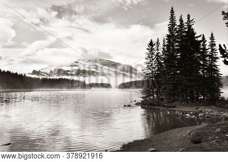 Two Jack lake with snow mountain and water reflection in Banff National Park in Canada.