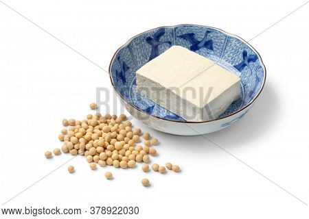 Piece of fresh white silk tofu in a Japanese bowl and dried soybeans isolated on white background