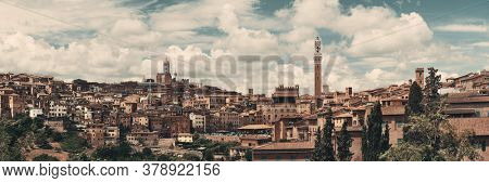 Siena Cathedral and Torre del Mangia Bell Tower with historic buildings. Italy