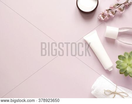 Care Products Lotion, Cream, Plant, Towel. Bath Accessories On Pink Background, Top View, Copyspace.