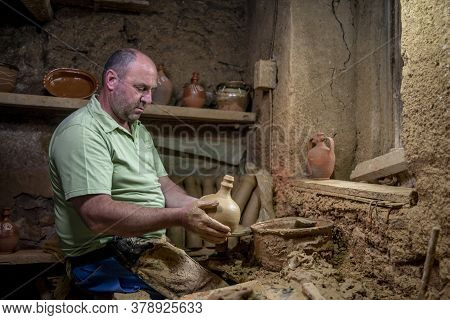 Male Potter Makes A Pot On The Pottery Wheel. Terracotta Pottery Guy On Spinning Wheel. Men Making I