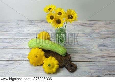 Green Squash And Yellow Mini Patty Pan Squashes On Wooden Table. Beautiful Yellow Flowers In A Glass