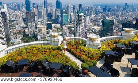 Thailand, Bangkok, January, 2020 - Happy Girl On The Roof Of Lebua Hotel Against The Background Of B