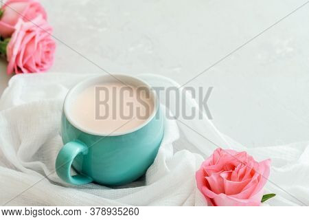 Cup Of Moon Milk With A Roses On On Light Concrete. Ayurvedic Relaxing Drink For The Night.