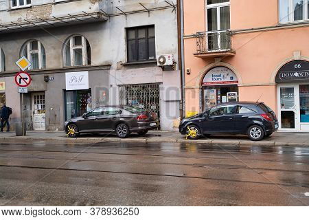 Krakow, Poland - July 18, 2020: Two Cars Locked With Clamped Vehicle Wheel Lock By The Street In Eur