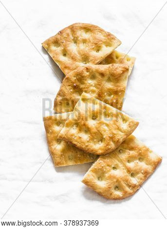 Slices Of Crispy Thin Italian Focaccia On A Light Background, Top View