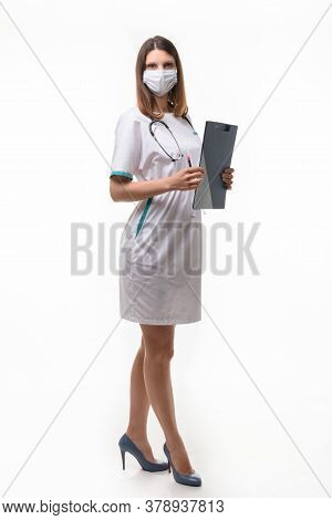 Girl Doctor In Medical Clothes And Mask With Tablet In Hand On White Background Builds In Full Growt