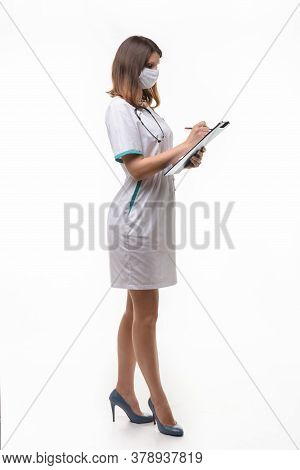 A Girl In Medical Clothes And A Mask Stands Sideways And Writes In A Tablet Information On A White B