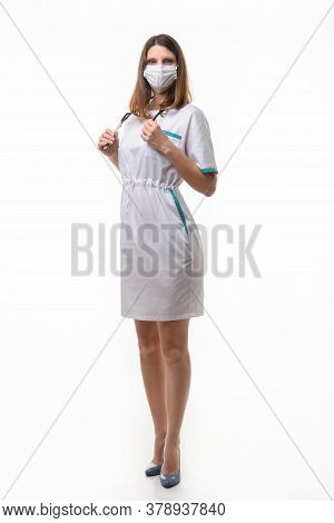 A Girl In Medical Clothes And A Mask Holds A Stethoscope On A White Background