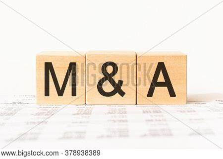 M And A Or Merger And Acquisition Text Written On A Wooden Cubes. Business Management And Marketing