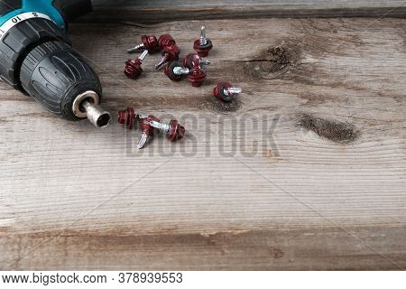 Cordless Drill Screwdriver And Self-tapping Screws For Metal On An Old Wooden Background With A Plac