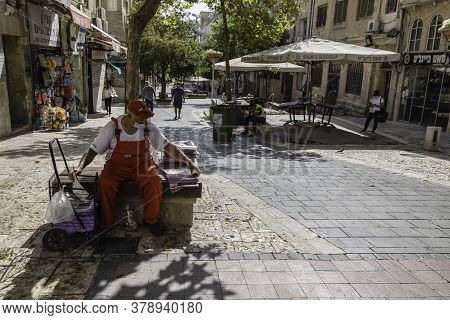 Jerusalem, Israel - July 30th, 2020: A newspaper man and a street cleaner sitting idly on Ben - Yehuda pedestrian mall, usually a crowded main street of Jerusalem, almost empty at COVID times.
