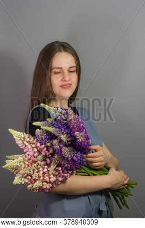 Brunette Florist Girl With Bouquet Of Multi-colored Lupins On Gray Background, Woman Florist With Bo