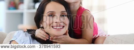 Portrait Of Joyful Mom With Child Sitting On Sofa At Home. Smiling Mummy And Little Kid Looking At C