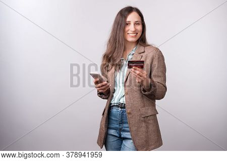 Cheerful Young Woman In Casual Showing Her New Debit Card And Smiling