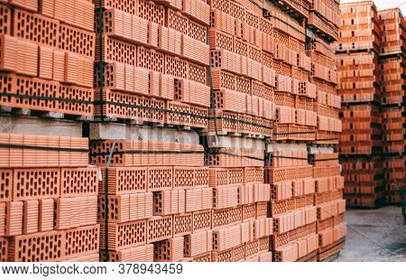 Stacks Of Orange Clay Brick On Pallet. Brick Production Concept. High Quality Photo