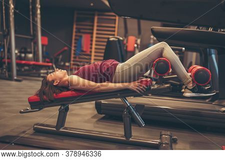 Active Young Woman Working Out In Gym, Doing Incline Bench Sit Ups, Strengthening Core And Abdominal