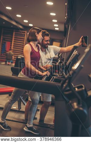 Young Couple Working Out In Gym, Taking A Break From Running On Treadmill, Relaxing And Taking A Sel