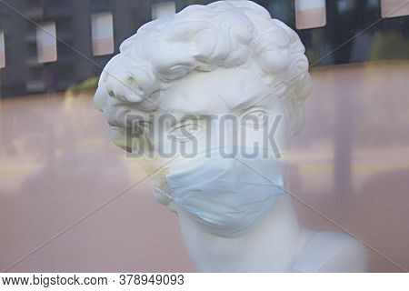 A Man, Woman Plaster Bust In A Protective Medical Mask Behind A Plate-glass Window With Reflection O