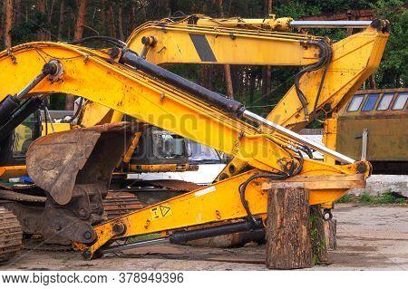 Old Broken Excavator Is Being Repaired. Rusty Metal, Remnants Of Old Yellow Paint, A Broken Bucket.