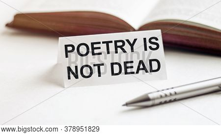 Piece Of Paper With Text Poetry Is Not Dead On The Background Of Books, Pens, On A White Background