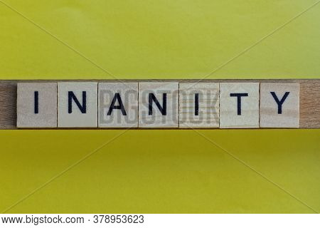 Gray Word Inanity In Small Square Wooden Letters With Black Font On A Yellow Background