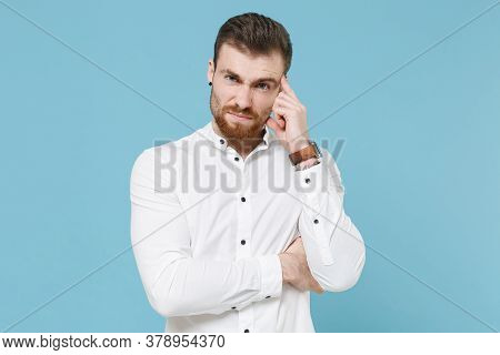 Displeased Puzzled Young Bearded Man Guy 20s In White Classic Shirt Isolated On Pastel Blue Backgrou