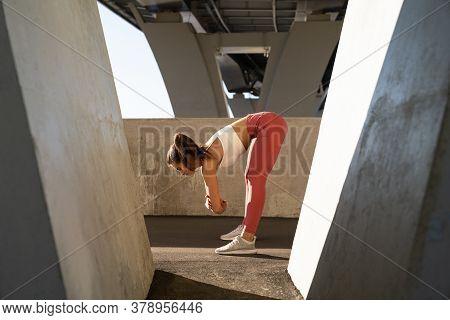 Slim Sportswoman In Pink Legging Standing Under The Bridge, Stretching Muscles Making Functional Tra