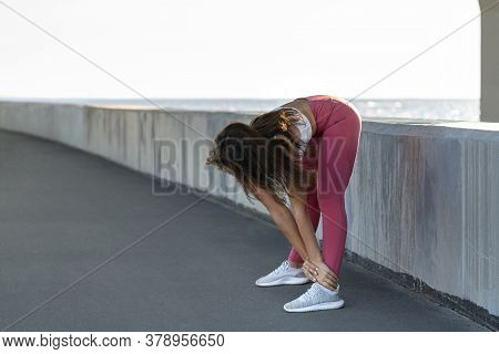 Athletic Woman In Pink Legging Standing On Embankment, Stretching Muscles Making Functional Training