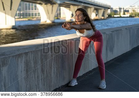 Fit Young Athletic Woman Extends Her Arms In Front Of Her And Performs Bends. Fitness Female In Pink