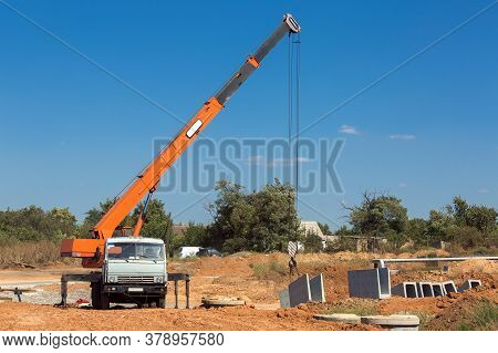 Truck Crane With Hydraulic System Lifts Concrete Structures For Construction Of Drainage System In T