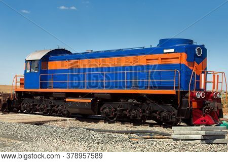 A Blue Shunting Diesel Locomotive With An Orange Stripe, A Deck Type Locomotive Stands On A Railroad