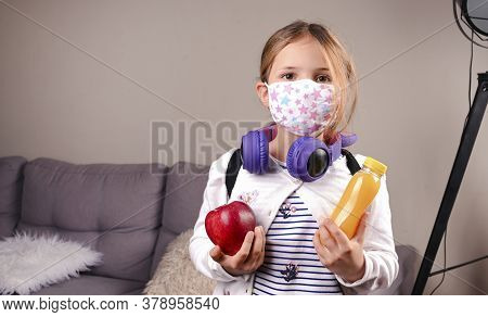 Little Girl Protective Mask. Got Ready To Go To School. Schoolgirl With Lunch In Hand, Books For The