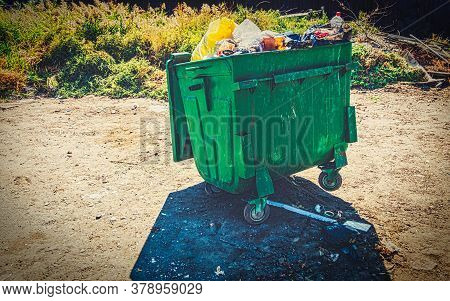 Overfilled Trash Dumpster Painted In Green Color In Ghetto Surrounding