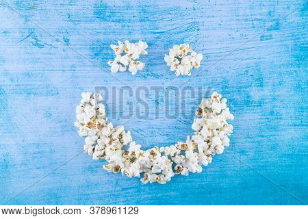 Pop Corn As Happy Face On A Blue Background And Copy Space