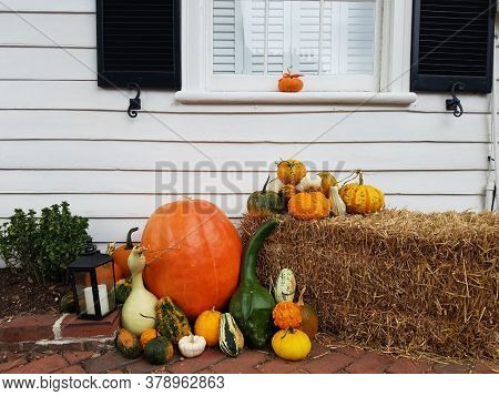 Pumpkins And Gourds On Hay Or Straw Bale And White House