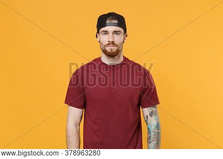 Handsome Young Bearded Tattooed Man Guy In Casual T-shirt, Black Cap Posing Isolated On Yellow Wall