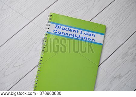 Book About Student Loan Consolidation Isolated On Wooden Table.