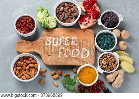 Various Superfoods On Grey Background.