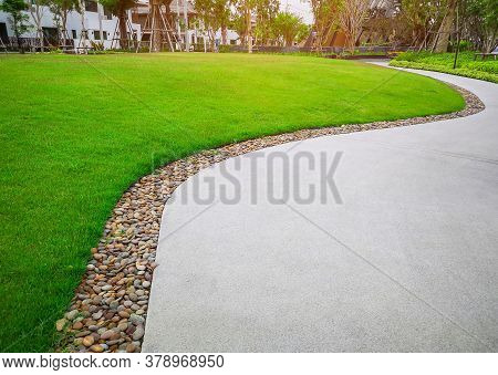 Smooth Green Grass Lawn And Gray Curve Pattern Walkway, Sand Washed Finishing On Concrete Paving Wit