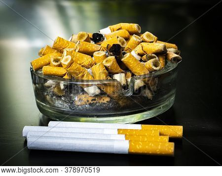 Glass Ashtray With Cigarette Butts On A Black Background.