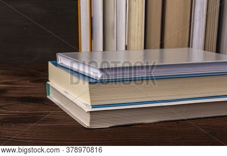 High Angle Close Up Of Stack Of Books Pile On Wooden Surface Against The Background Of Books Standin