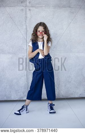 Frontal Portrait Of A Smiling Little Girl In Blue Uniform, In Red Eyeglass, Back To School Concept.