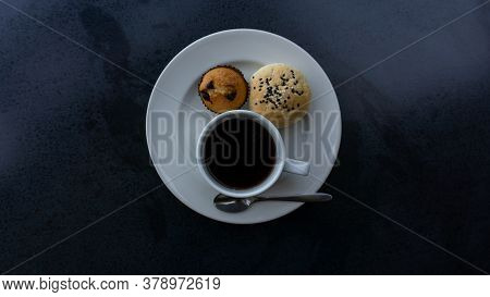 Top View Photo, A White Cup Of Americano Black Coffee, Cup Cake And Cereal Bread On White Plate On B