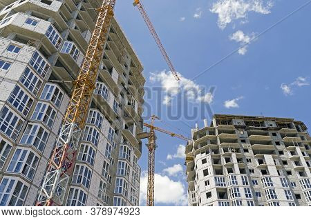 Building Crane And Building Under Construction Against Evening Blue Sky