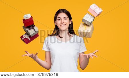 Holiday Shopping. Discount Sale. Amused Woman In White T-shirt Throwing Up Gift Boxes In Air Isolate