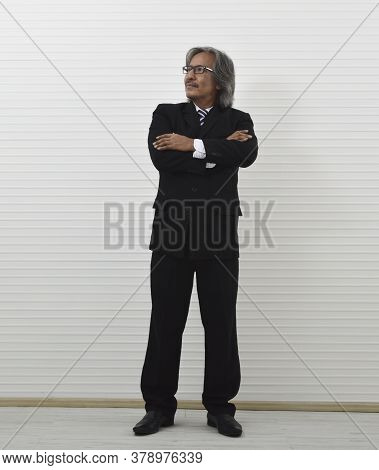Happy Elderly Asian Businessman In Black Suit And Eyeglasses Posing With Arms Crossed Standing Over