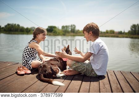 Brother and sister enjoying on the dock of the lake with their dog