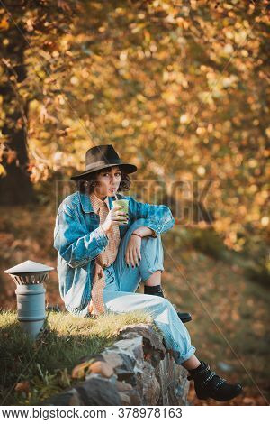 . Young Woman Enjoying Autumn Weather. Dreamy Beautiful Girl With Natural Black Hair On Autumn Backg